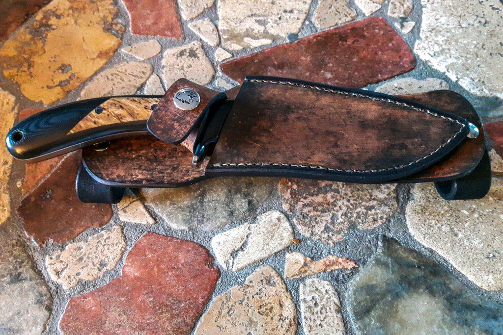 A custom leather sheath over a survival knife by Sandstorm Custom Knives.
